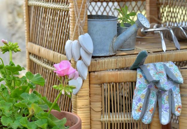 Guanti da giardinaggio e altri accessori su un piccolo mobile in vimini all'aperto in terrazza