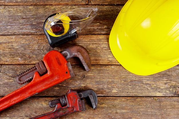 Guanti da lavoro in pelle e cappello gialli e costruzione chiave inglese