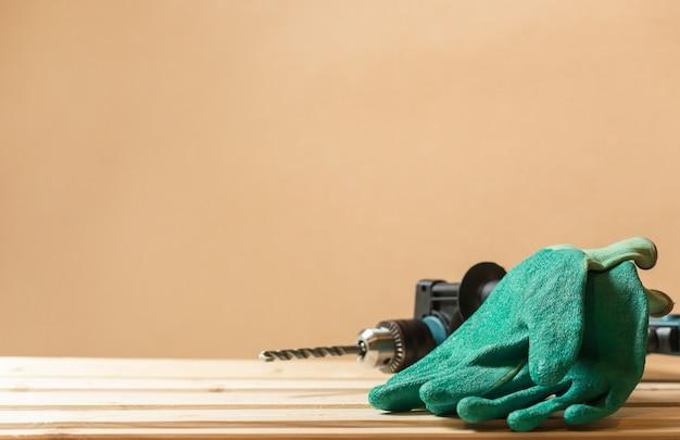 Guanti da lavoro verdi con trapano a percussione sul rivestimento del tavolo in legno e copia spazio muro. concetto di protezione dei lavoratori.