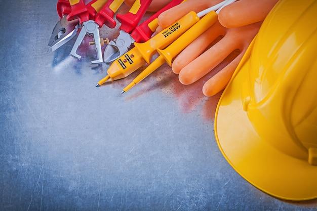 Guanti degli elettricisti che costruiscono gli estrattori elettrici dell'isolamento delle pinze delle pinze del tester del casco sulla tavola metallica