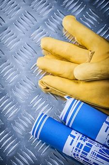 Guanti di sicurezza di cuoio dei disegni di ingegneria blu sul concetto di piastra metallica ondulato della costruzione