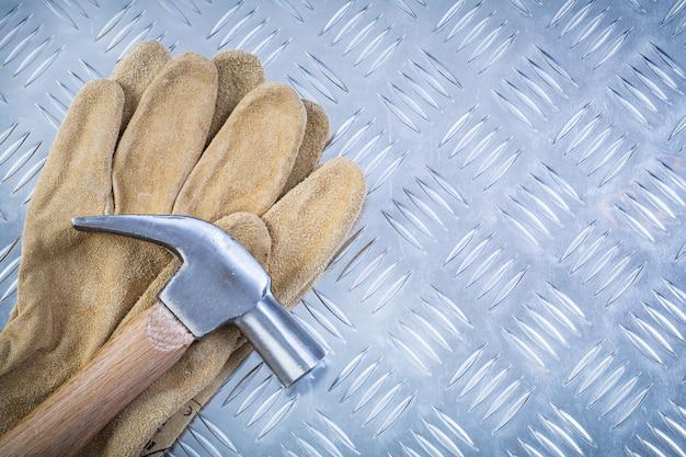 Guanti di sicurezza in pelle martello da carpentiere sul concetto scanalato della costruzione della lamina di metallo