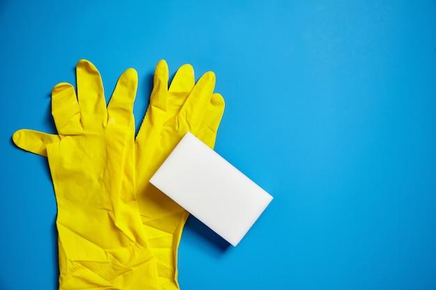 Guanti gialli e spugna melaminica bianca su sfondo blu. strumento universale per pulire varie superfici