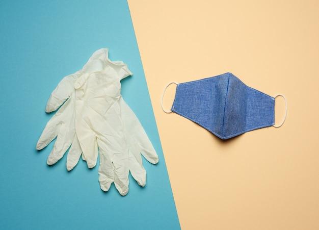 Guanti in lattice bianchi e maschera riutilizzabile blu in tessuto su fondo beige blu