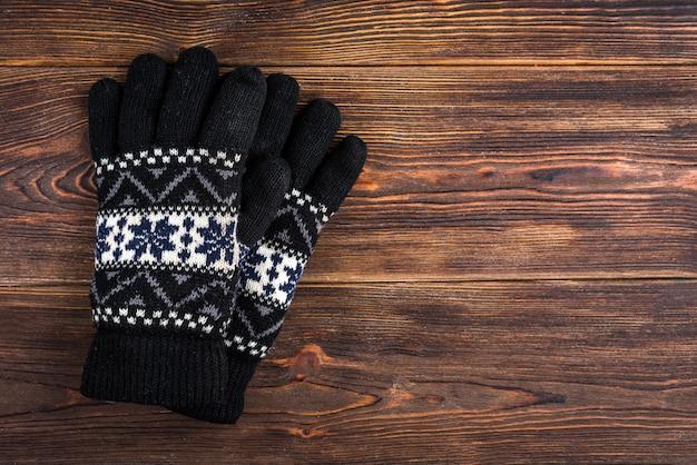 Guanti lavorati a maglia invernali su legno scuro.