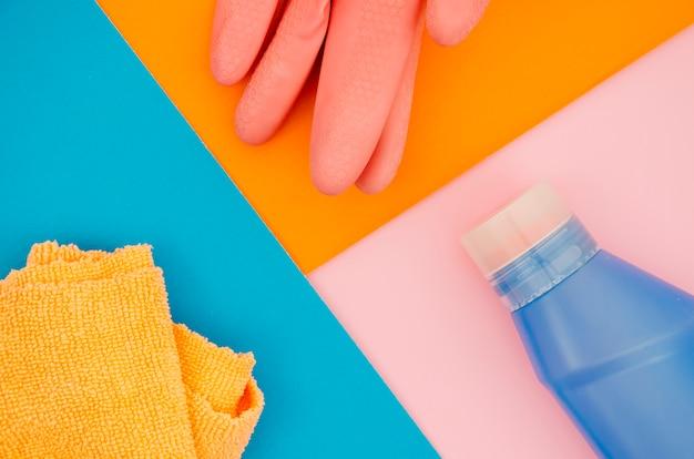 Guanti; tovagliolo e bottiglia su un'arancia; sfondo blu e rosa