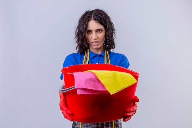 Guanto da portare dispiaciuto e guanti di gomma della giovane donna dispiaciuti che tengono secchio con gli strumenti di pulizia con il fronte serio sopra la parete bianca