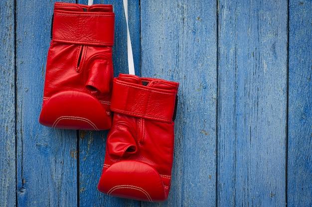 Guantoni da boxe in pelle rossa che appendono su una corda