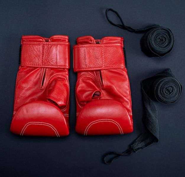 Guantoni da boxe in pelle rossa e fasciatura tessile nera
