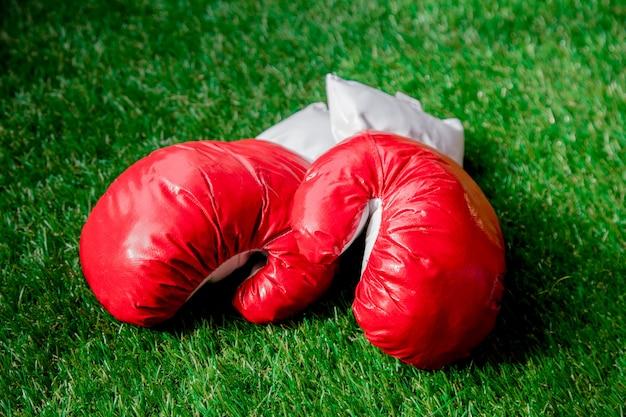 Guantoni da boxe rossi su erba verde.