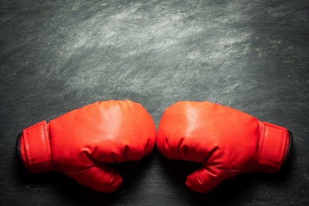 Guantoni da boxe su sfondo di cemento nero. concetto di combattimento o boxe.