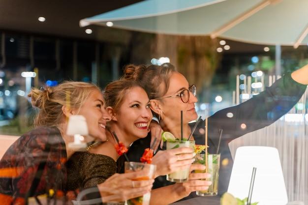 Guarda attraverso un bicchiere di donne che fanno un selfie e bevono cocktail in un ristorante di notte