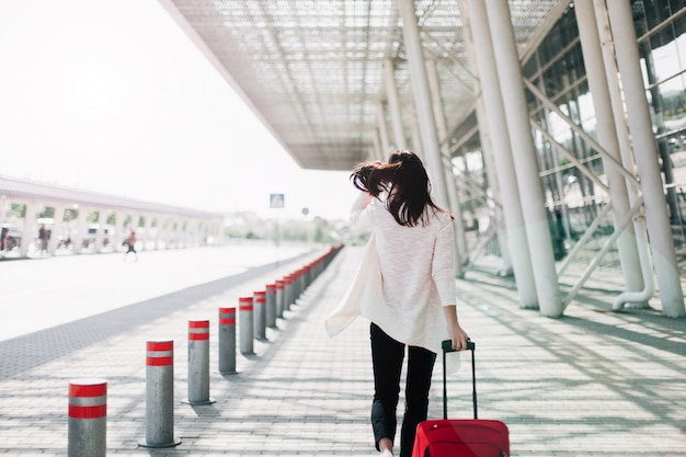 Guarda da dietro a una donna con valigia rossa che cammina lungo l'aeroporto