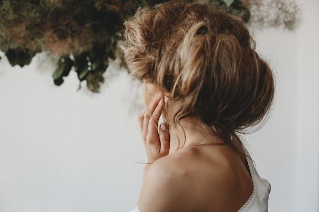 Guarda da dietro la donna con i capelli biondi raccolti sulla sua testa