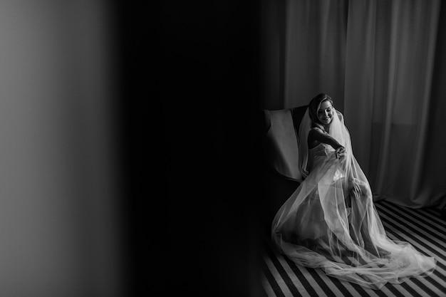 Guarda da dietro la porta l'affascinante sposa seduta su una grande sedia
