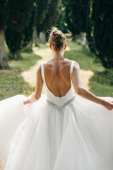 Guarda da dietro la sposa in abito con la schiena nuda che corre lungo