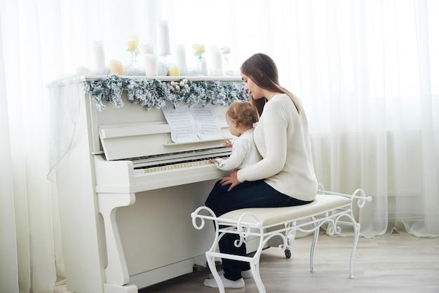 Guarda da dietro madre e figlia che suonano il pianoforte bianco