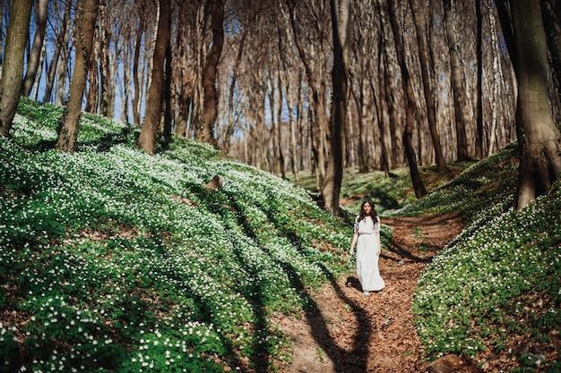 Guarda da lontano la donna in bianco che cammina nella foresta verde
