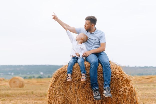 Guarda il cielo! padre e figlio seduti su un pagliaio o un fieno arrivano a fiumi un campo che punta verso il cielo su un aereo o qualcosa che vola.