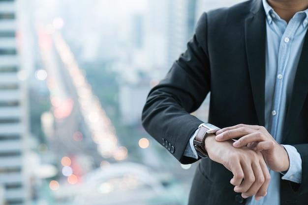 Guarda il designer di primo piano sulla mano dell'uomo d'affari, guarda il tempo e si affretta