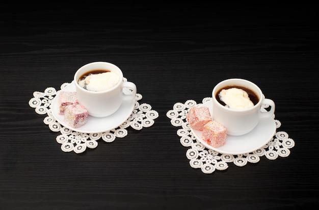 Guarda in un angolo in due tazze di caffè con gelato