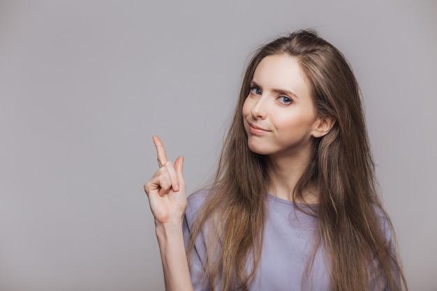 Guarda qui! il modello femminile castana adorabile con lo sguardo attraente, indica con il dito anteriore lo spazio in bianco della copia