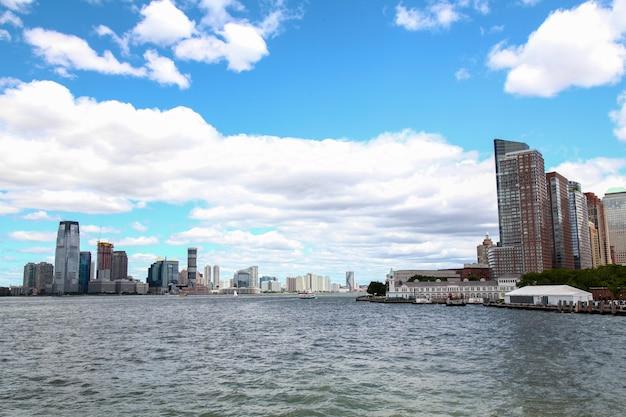 : guarda sulla barca a vela che sta navigando negli edifici portuali di new york dell'isola di manhattan in background.