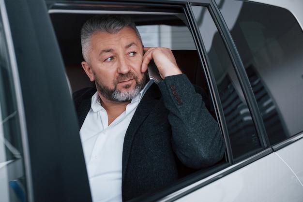 Guardando attraverso la finestra della porta aperta. avere una chiamata di lavoro mentre era seduto sul retro di un'auto di lusso moderna