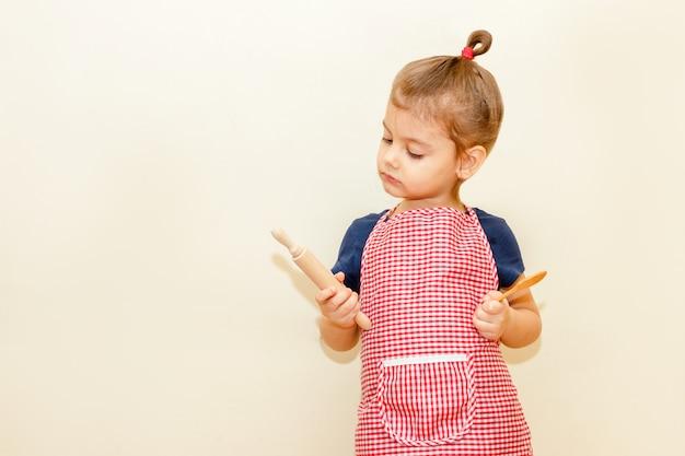Guardando con interesse la bambina con il grembiule del cuoco unico che tiene il matterello di legno e un cucchiaio su fondo beige