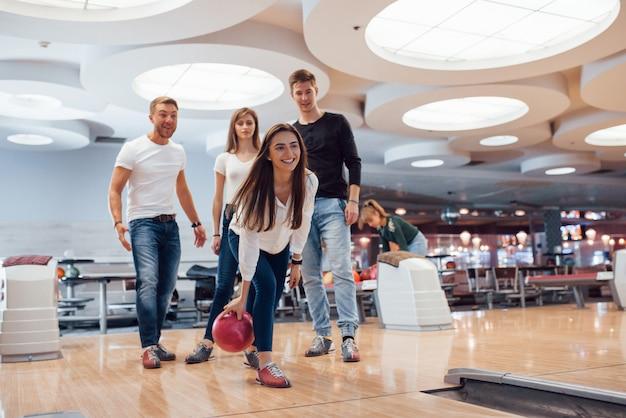 Guardando dritto in avanti. i giovani amici allegri si divertono al bowling durante i fine settimana