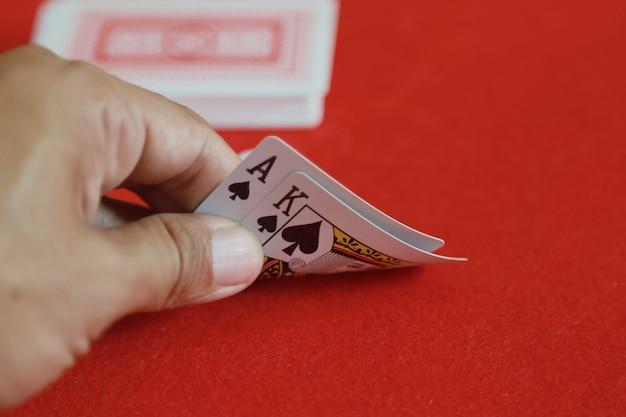Guardando le carte in mano sul gioco di carte da gioco del blackjack nel casinò