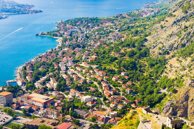 Guardando oltre la baia di kotor in montenegro con vista sulle montagne, barche e vecchie case con tetti di tegole rosse