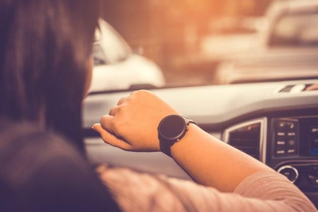 Guardando orologio, orologio, orologio a portata di mano alla guida di auto sulla strada e ingorgo