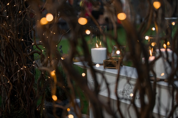 Guardate i rami lucidi al tavolo bianco con le candele