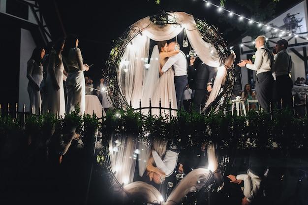 Guardi da dietro l'altare di cerimonia nuziale alle coppie di nozze allegre durante la cerimonia