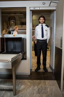 Guardia di sicurezza in piedi sotto la porta di scansione