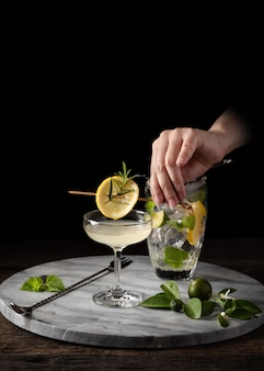 Guarnire il cocktail con la mano del barista sul bancone con setaccio e attrezzatura da bar