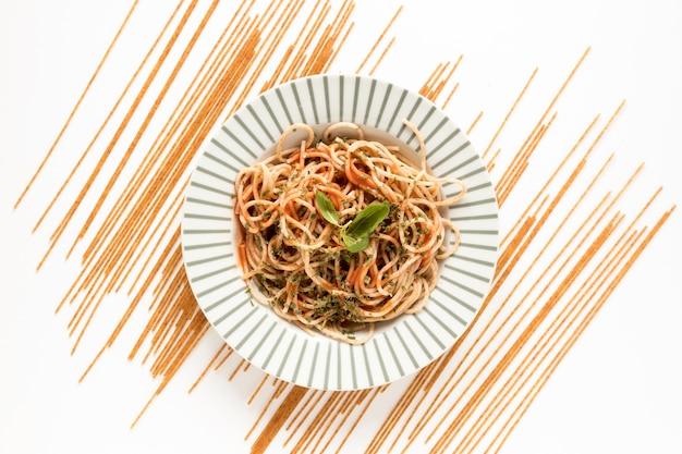 Guarnire la pasta degli spaghetti con pasta cruda sulla superficie bianca
