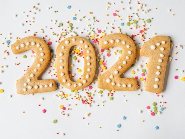 Guarnizione e pan di zenzero colorati multi dello zucchero della pasticceria sotto forma di numeri 2021 su un fondo bianco