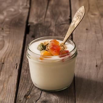Guarnizioni dei semi di zucca, dell'avena e della frutta su yogurt nel barattolo di vetro sulla tavola di legno