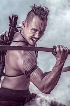 Guerriero antico tailandese del ritratto che tiene una spada a due mani.