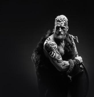 Guerriero medievale vichingo con barba tatuaggio e trecce nei capelli con ascia e scudo