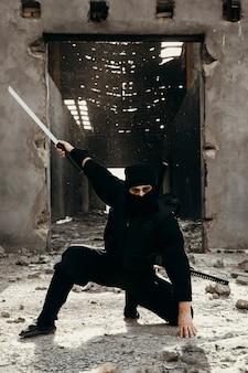 Guerriero ninja in abiti neri con un dispiacere
