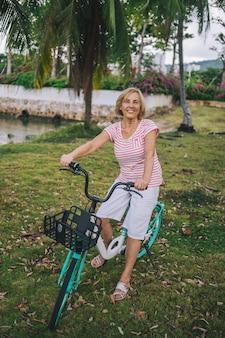 Guida ambulante turistica di viaggio sorridente attiva asiatica senior anziana della donna in bicicletta che gode nella giungla tropicale di sanya. in viaggio lungo l'asia, concetto di stile di vita attivo. alla scoperta di hainan, in cina