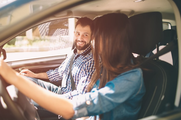 Guida attenta. belle giovani coppie che si siedono sui sedili del passeggero anteriore e che sorridono mentre donna che guida un'automobile