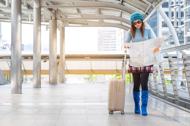Guida di viaggio. giovane viaggiatore femminile con lo zaino e con la mappa sulla strada.