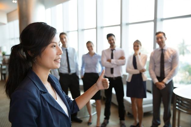 Guida femminile di affari con il pollice alto