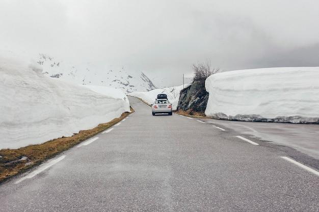 Guida in auto attraverso una strada pulita tra una grande nevicata