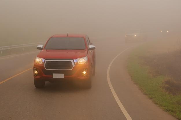 Guidare auto nella montagna di nebbia con fasci di faro in una fitta nebbia.