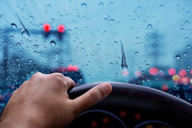 Guidare in un giorno piovoso. cattivo tempo sulla strada con luci sfocate e ingorghi in città